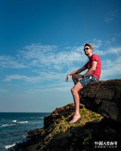 安德坐在澎湖景點海底郵筒附近的岩石上